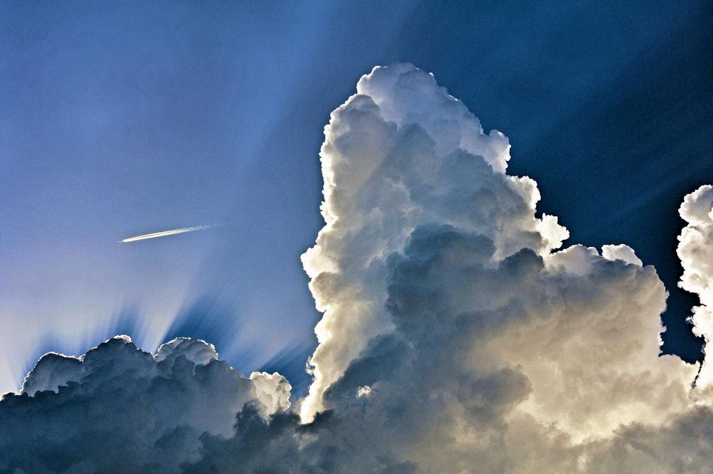 Wolken sonnenstrahlung und kondensstreifen aus der serie juliwolken